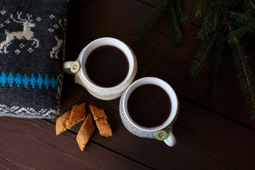 Cups of coffee or tea near cake and knitwear on wooden background. Winter concept
