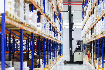 Warehouse worker on forklift pulls boxes from the top shelves in large, modern warehouse