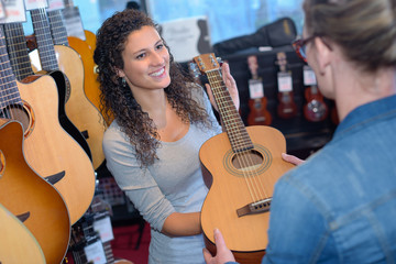 Poster Music store Woman passing guitar to customer