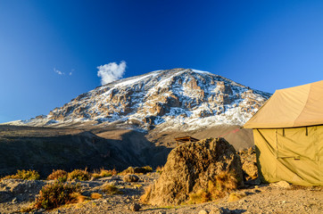Stunning evening view of Kibo with Uhuru Peak (5895m amsl, highest mountain in Africa) at Mount Kilimanjaro,Kilimanjaro National Park,seen from Karanga Camp at 3995m amsl. Navy tent in foreground.
