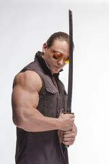 Portrait of a brutal man bodybuilder in sunglasses with a sword on a white background