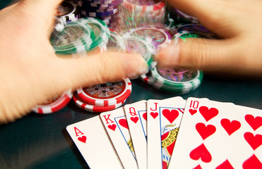 Royal flash win in poker and female hands grabbing bank. Blurred motion.