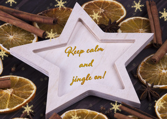 Christmas Xmas New Year Holiday greeting card with wooden star cinnamone star anice dried oranges snowflakes and text Keep calm and jingle on