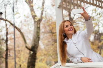 Happy fashion woman in fall autumn park taking selfie self photo