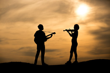 silhouette of musician with guitar play and violin player at sunset
