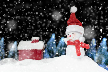 Snowman on snow pile and bokeh tree on dark night background hol