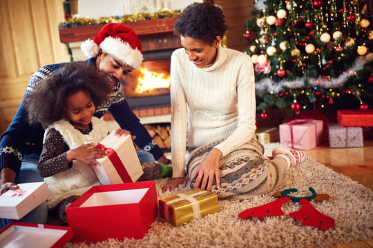 afro American family in Christmas morning opening present.