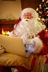 Real Santa Claus using laptop to communicating with children