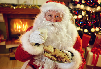 Santa Claus enjoying in cookies and milk.