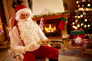 Santa Claus resting in warm room and eating traditional Christma