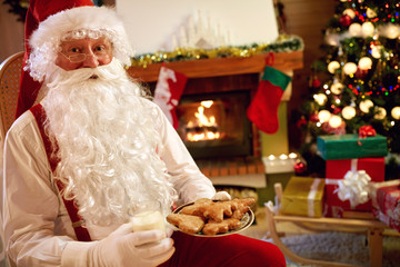 portrait Santa Claus sitting and enjoying in cookies and milk.
