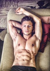 Shirtless sexy young man in panties relaxing on sofa and looking at camera. From above