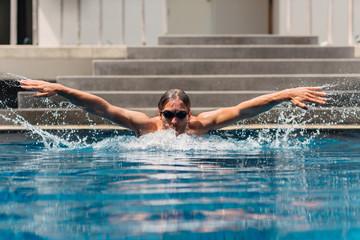 Taking breath swimming butterfly in pool