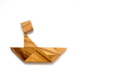 Wooden tangram as man scull boat shape on white background
