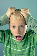 Young Blond Boy Tearing His Hair Out Because Of Stress