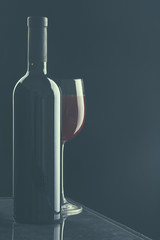 Glass of wine and a bottle on black background
