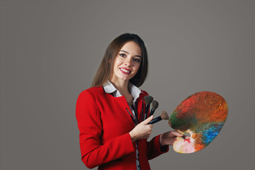 Cheerful beautiful young woman makeup artist on a gray background , with palette in hand