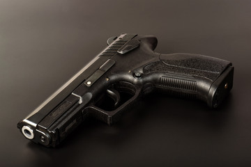 The black gun (pistol) on a dark background close up. Isolate.