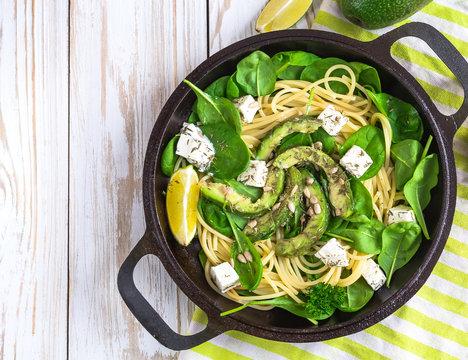 fettuccine pasta with sliced avocado, feta cheese, spinach