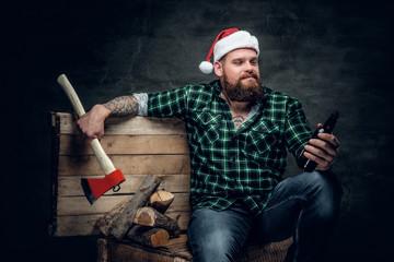 Fatty bearded male in Santa's hat, drinking beer.
