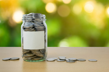 Money bottle with coins on bokeh background