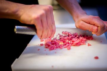 Chef mincing raw meat to prepare a steak tartare