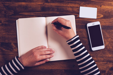 Woman writing contact list from phone into business agenda