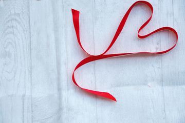 Romantic background ;  a ribbon in shape of heart on a white wooden background