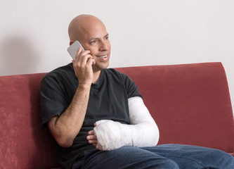 Young man with an arm cast talking on his phone