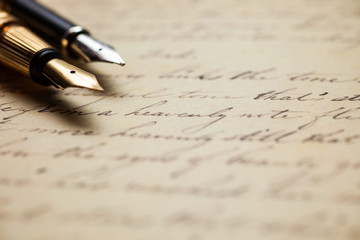Fountain pens on an antique handwritten letter