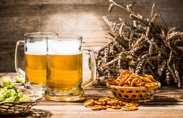 Two mugs of foam beer with pretzels, wheat and hops