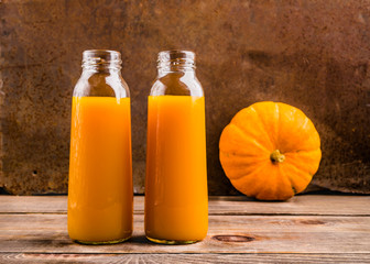 Fresh pressed juice from ripe pumpkin in transparent glass bottl