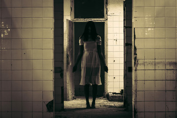 Horror scene of haunted woman in white dress in the demolished building