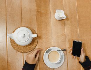 Woman with smartphone taking hot tea or coffee with milk in a cup on wooden table background. Flat closeup view