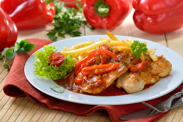 Deftiges Zigeunerschnitzel mit Pommes Frites vor roten Paprikaschoten - Hot escalope with red pepper sauce and French fries