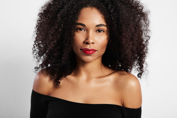black woman watching at camera directly, curly hair