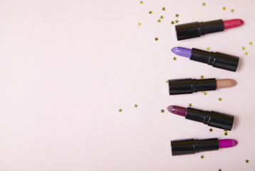 Overhead view of assorted color lip stick make up on a pastel pink background with gold glitter stars and empty space at side