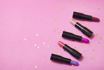 Assorted color lip stick cosmetics on a bright pink background with gold glitter stars and blank space at side