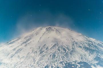 雪煙舞う月下の富士