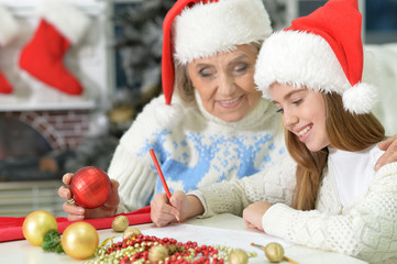 Grandmother with girl preparing for Christmas