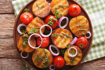 Healthy food: grilled potatoes and tomatoes with herbs and onion close-up on a plate. horizontal top view
