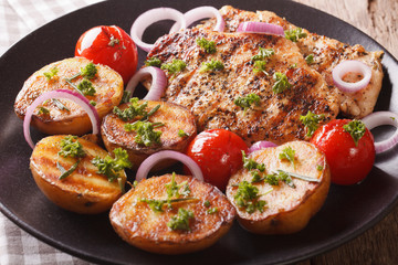 Chicken meat grilled with new potatoes and tomatoes close-up. horizontal