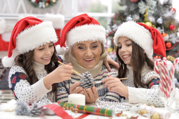 Grandmother with girls preparing for Christmas