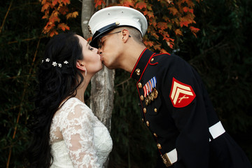 Sailor of US Army kisses bride tender standing before an autumn