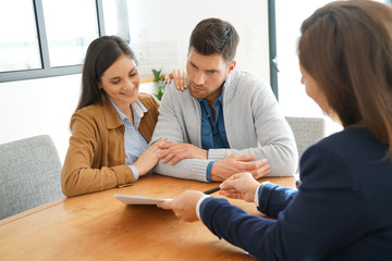Couple meeting financial adviser for home investment contract