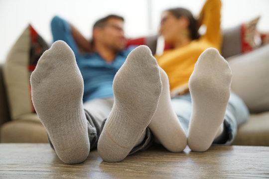 Closeup of couple's feet laid on table