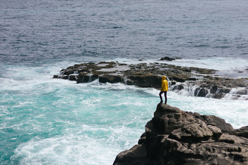 man on cliff above ocean
