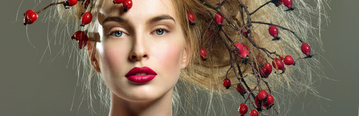 Beautiful woman with a wild rose branches on head. Red berries i
