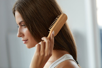 Woman Brushing Beautiful Healthy Long Hair With Brush Portrait