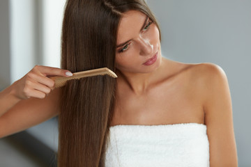 Brushing Hair. Woman Hairbrushing Beautiful Long Hair With Comb